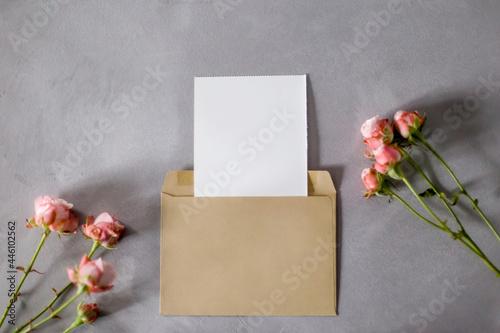 Obraz na plátne Envelope, sheet of paper and roses on a gray background