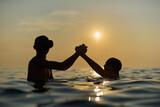 Młodzi przyjaciele kąpią się w morzu o zachodzie słońca. Sepia, backlight, silhouette.