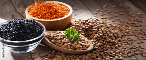 Obraz na plátně Composition with three sorts of lentils on wooden table
