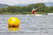 A Yellow Buoy Is Floats On A Surface Of Water In A Lake With A Surfer On A Background.