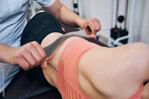 Fotografie, Obraz Male chiropractor is treating woman abdominal muscles