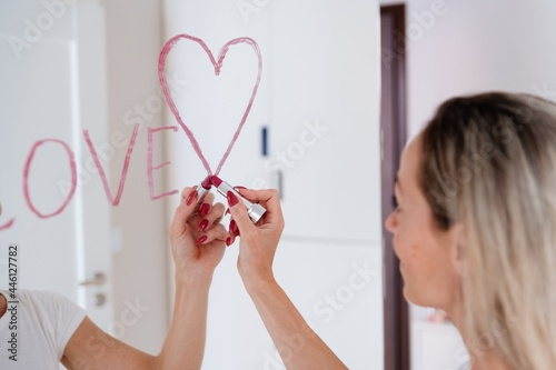 Fotografie, Obraz A blonde woman draws the inscription love and a heart with lipstick on the mirror