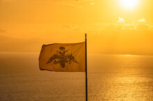 The Byzantine Empire Flag Waving Over The Messenian Gulf Against The Yellow Sky At Sunset. The Double-headed Eagle Is A Charge Associated With The Concept Of Empire