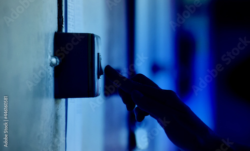 Fotografia Homeowner is turning off the light switch on the wall of the house, concept for saving money and protect surrounding environment