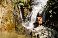 Young Athletic Man With Dreadlocks Crouching Down Watching A Magnificent Waterfall