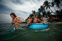 Group Of Surfers Ride On Vietnam Wooden Boat To Surf Session On Coastal Vilage