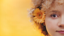 Half Face Shot Of A Beautiful Young Girl With Curly Hair And Orange Gerbera Daisy Flower On Her Ear Posing For The Camera. Isolated Over Bright Yellow Background Studio. Closeup View.
