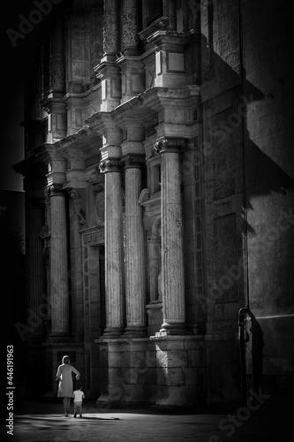 Canvas-taulu Frau und Kind vor Kirchenportal in Spanien schwarz-weiss