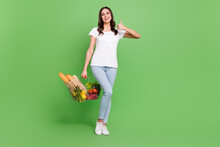 Full Size Photo Of Funny Brunette Young Lady Hold Food Show Thumb Up Wear T-shirt Jeans Isolated On Green Color Background