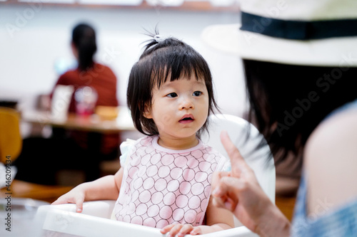 Wallpaper Mural Asian baby girl listening acknowledge to her mother speaking during launch time in restaurant