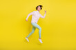 Leinwandbild Motiv Full length body size photo of cheerful model jumping high running fast smiling isolated vivid yellow color background
