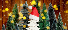 Many Different Christmas Trees With Golden Lights And Santas Red Hat On A White Tree. Merry Christmas And A Happy New Year Banner. Seasons Greetings Card