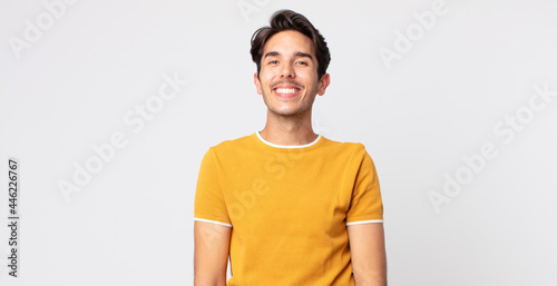 Obraz na plátně hispanic handsome man looking happy and goofy with a broad, fun, loony smile and