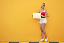 Your Text Here. Colorful Studio Portrait Of Pretty Young Woman Showing Empty Blank Board With Copy Space Against Yellow Wall.