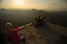 Hampi, India - 5 Dec. 2014:  People At The Top Of Cliff On Sunrise And Green Rice Field