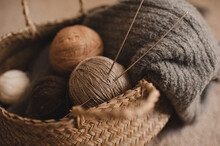 Yarn Balls With Knit Cloth Fabric And .knitting Needles In Straw Basket In Room. Winter Season. Cozy Warm Home Atmosphere.