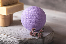 Decorative Lilac Ball Wrapped, Intertwined, Interlaced, Coiled In Threads On Rustic Wood Podium Near The Paper Flowers And Handmade Soap. Closeup, Selective Focus