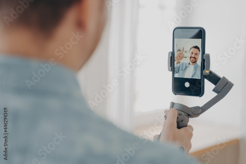 Fototapeta Handsome smiling young brunete man with stubble making selfie on smartphone