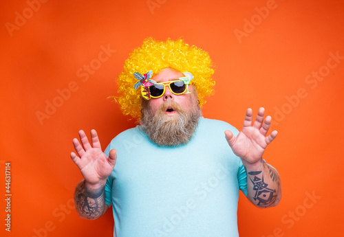 Fototapeta Fat amazed man with beard, tattoos and sunglasses has fun with the yellow wig