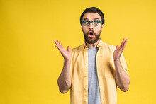 Happy Winner! Portrait Of Shocked Amazed Young Male Man Keeps Mouth Widely Opened, Being Surprised, Expresses Great Surprisment. Isolated Over Pink Yellow Background.