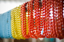 Strings Of Blue, Yellow And Orange Beads Hand In A Second Hand Shop In The Les Puces Flea Market In Paris, France.