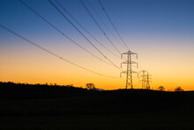 A Winter Sunset Behind Electricity Power Lines And Pylons At Milton Near Brampton, Cumbria UK
