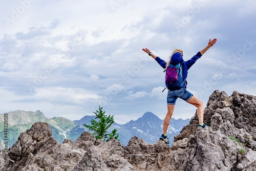 Fotografie, Obraz Blonde woman tourist standing on a rock with his arms spread wide looking in the distance