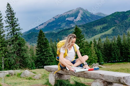 Obraz na plátně Female tourist with backpack sits on a bench with a paper map in mountain