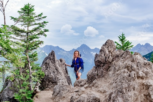 Fototapeta Smiling blond hiker is standing on the mountain trail in the high mountains