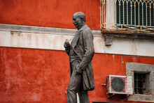 Statue Of The Economist And Politician Antonio Scialoja (1817-1877) In Martyrs' Square, On A Red Background, Procida Island, Province Of Naples, Italy