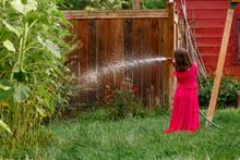 Rear-view Of Girl In Long Red Dress Watering Roses In Backyard Garden