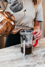 Woman Pours Hot Water From Teapot Into A French Press To Make Coffee