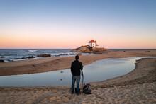 Man Photographing Beautiful Senhor Da Pedra Chapel On The Beach