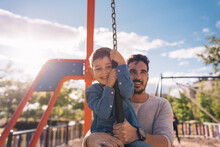 Father And His Son Playing With A Zip Line In A Park