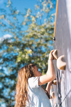 Little Girl Smiling While Climbing Wall In A Park