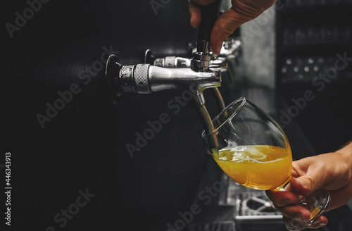 Foto bartender hand at beer tap pouring a draught beer in glass serving in a restaura