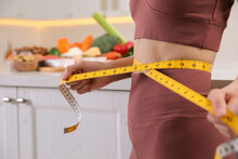 Woman With Measuring Tape In Kitchen, Closeup. Keto Diet