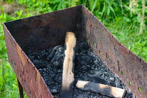 Fotografie, Obraz Unburned wood in an old rusty brazier