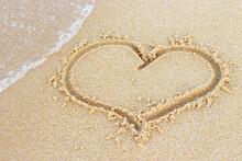 A Heart Shape Drawn On Sand On The Beach Close-up.