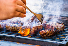 Preparing Meat Rolls Called Mici Or Mititei On Barbecue. Close Up Of Grill With Burning Fire With Flame And Smoke.