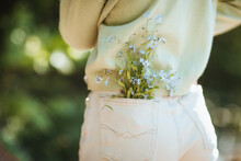 Unrecognizable Teen Girl With Flowers In Jeans Pocket