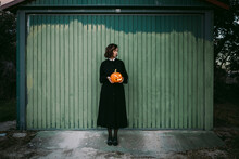 Woman With Halloween Pumpkin Standing Near House In Countryside