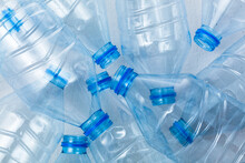 Plastic Bottles On A Blue Background As A Symbol Of Ecological Catastrophes. Empty Bottles From Water As An Advertisement For Recycling.
