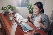 A Medium Shot Of An Excited Young Adult Asian Woman Doing Video Call Conference Meetings Over A Laptop Computer On A Wooden Table. She Is Enjoying Her Success.