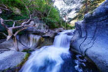 River Waterfall Among Rocks And Green Vegetation At Sunrise. Navacerrada.