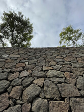 Low Angle Stone Wall Texture With Trees On The Top Under A Cloudy Sky