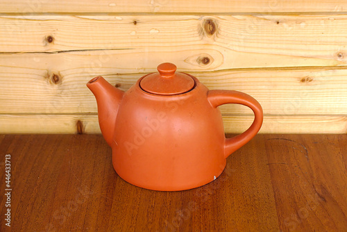 Fotografie, Obraz Ceramic teapot on a table against a wooden wall