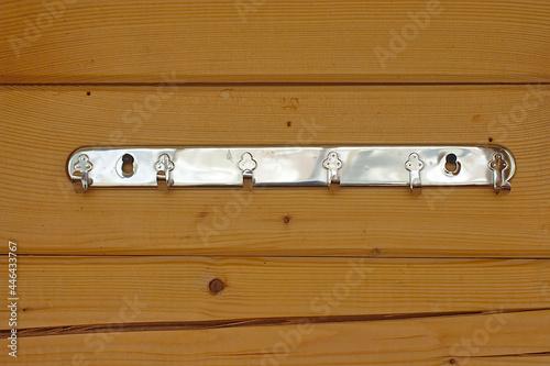 Fototapeta Metal hanger with hooks on a wooden wall
