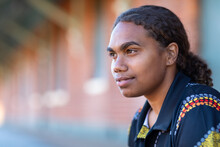 Head And Shoulders Of Indigenous Girl With Hair Tied Back And Blurry Building In Background