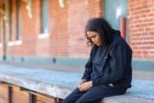 Teenager Dressed In Black Looking Down Sitting On Platform